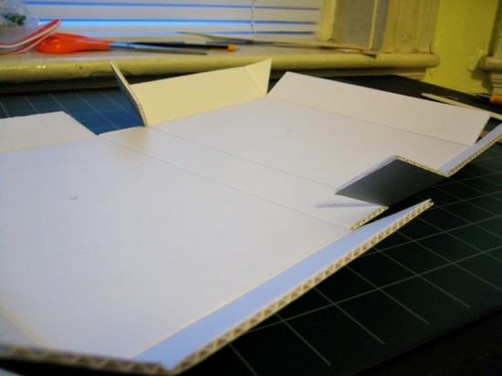 The cardboard has been creased. Next, the remaining pencil lines are erased and the corrugated middle is stripped from the triangular portions.
