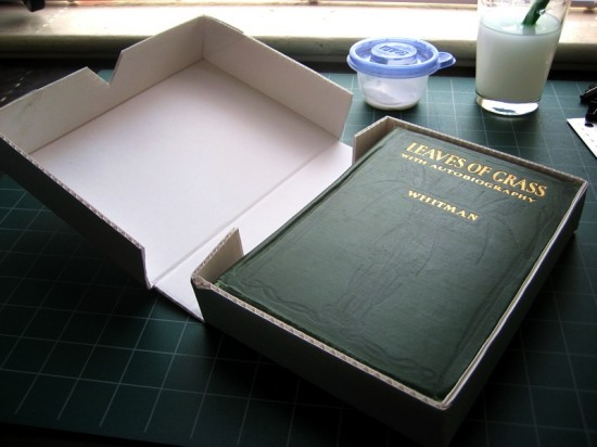 The opened box, with its book inside. It fits much better in this one.