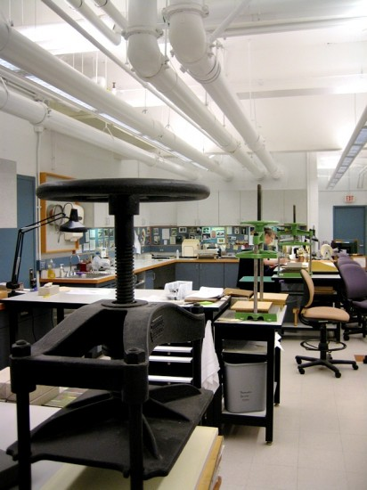 """A view down the length of the (""""C""""-shaped) lab. To the near right, Nancy is showing us some recent projects. To the immediate left are those recently conserved items mentioned above. To the far right would be the entrance to the lab and some general collections processing."""