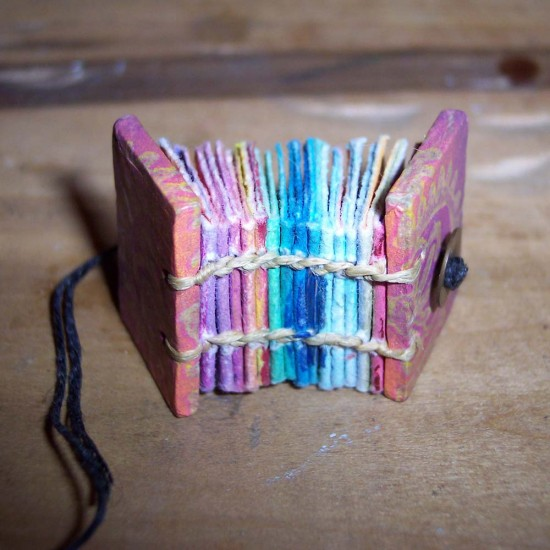 "This miniature book is bound in the Coptic style and uses some lovely colored paper. (Cat Sidh, ""100_4662,"" December 2, 2007, Creative Commons Attribution.)"
